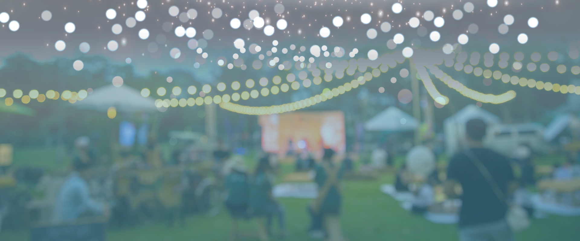 Outdoor event with fairy lights and picnic tables